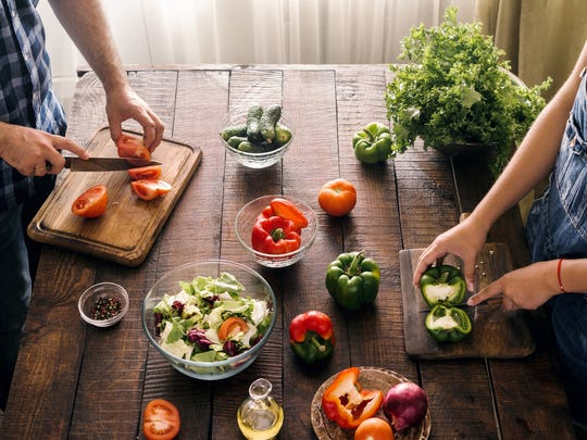 A couple preparing dinner with fresh ingredients.