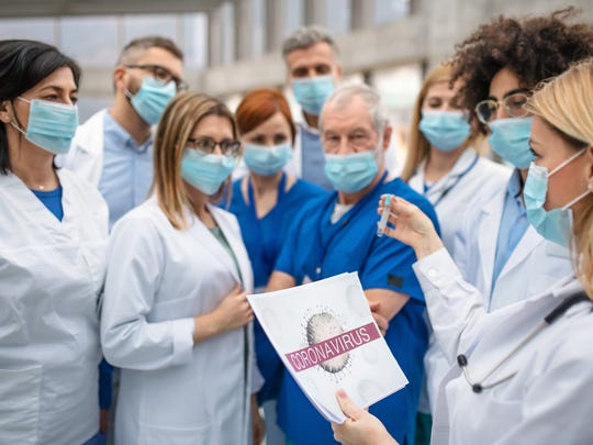 A group of doctors discuss the coronavirus outbreak outside a hospital.