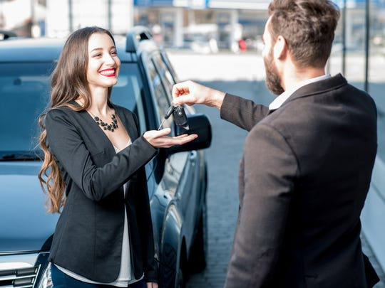A used car salesman hands keys to a smiling customer.