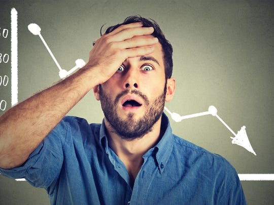 A man holds his forehead in his hand in front of a declining stock price chart.