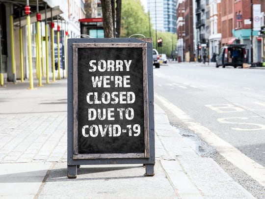 A foldable sign in front of a store that reads, Sorry We're Closed Due to COVID-19.