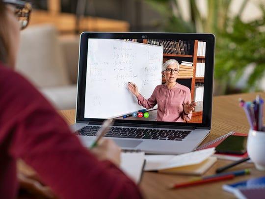 Student watching teacher on a laptop screen