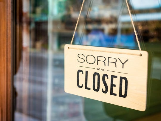 """A restaurant with a """"closed"""" sign in the window"""
