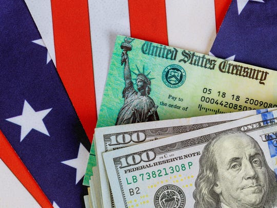 Stimulus economic tax return check and US 100 dollar bills currency with US flag.