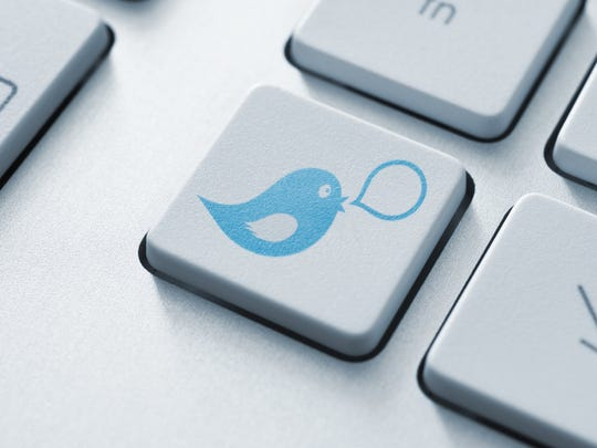 The blue Twitter bird icon imprinted on the key of a computer keyboard