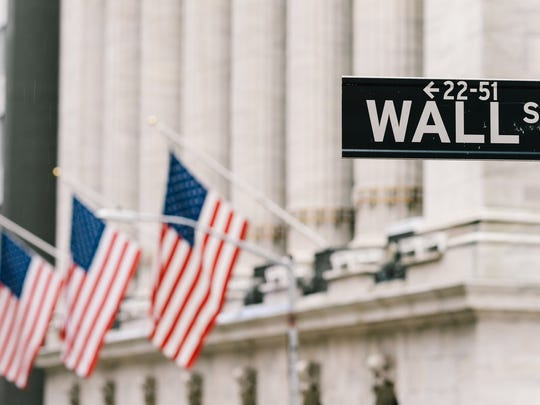 The Wall Street street sign shown in front of a Wall Street building with flags
