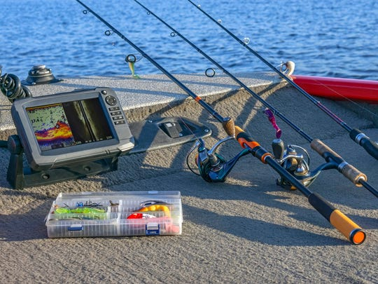Fishing rods, lures, and a fishfinder on the deck of a boat