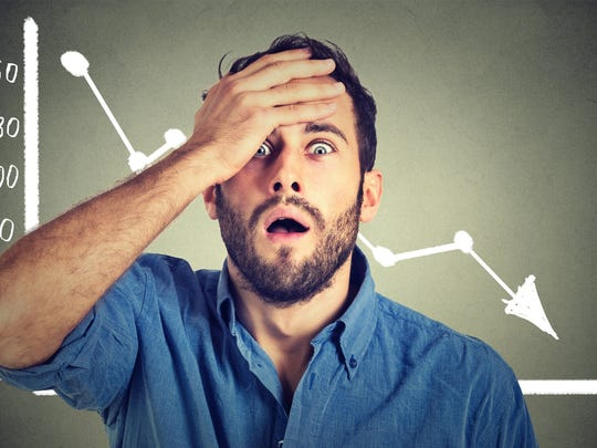 Man holding head in front of down stock chart