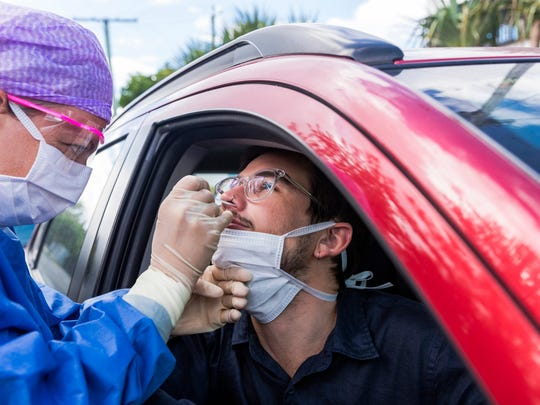 Man in a car getting a nasal swab test