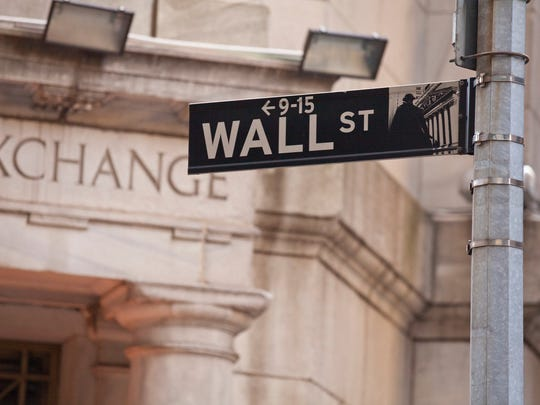The Wall Street sign post with the New York Stock Exchange behind it.
