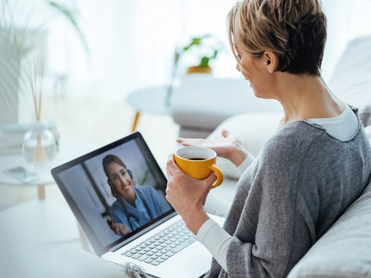 A woman sits on a white couch holding a mug and talking to another woman through a laptop video chat.