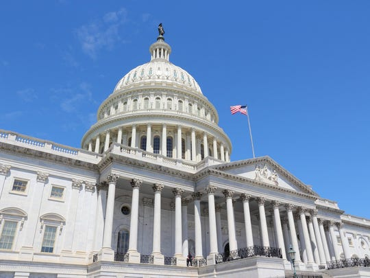 Front of U.S. Capitol Building, with U.S. flag prominently shown.