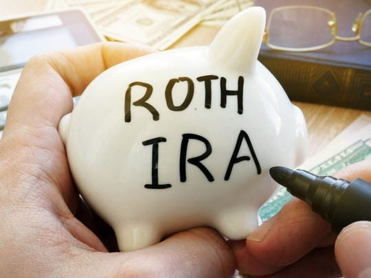 Hand holding piggy bank with Roth IRA written on it