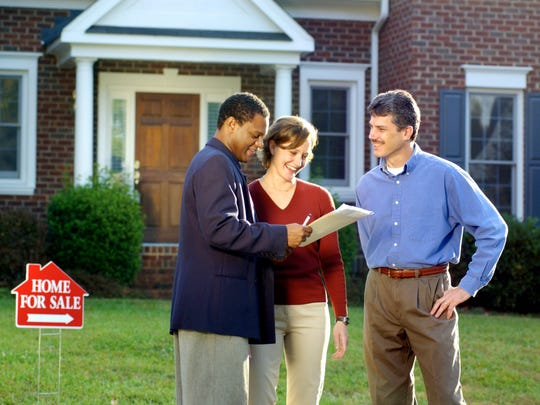 Three people standing in front of a house with a for sale sign on the lawn