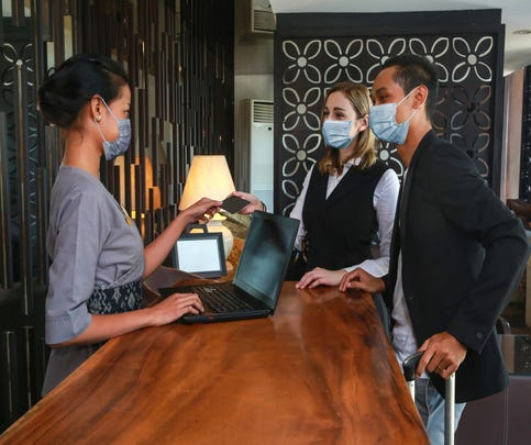 Man and woman wearing face masks booking a hotel room at front desk