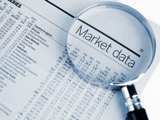 "A magnifying glass enlarging the words ""Market data"" in a financial newspaper."