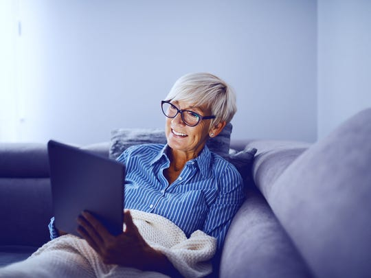 Smiling older woman holding tablet on couch