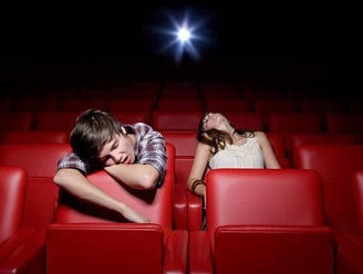 Two young theater goers asleep in an otherwise empty multiplex.