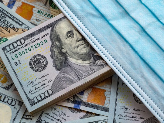 Stacks of $100 bills laid out with a medical mask on top.