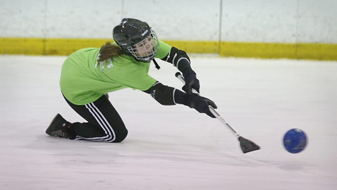 In broomball, players trade skates for sneakers and use brooms instead of hockey sticks to whack a grapefruit sized ball.