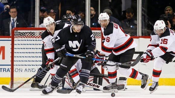 Devils center Jacob Josefson (16), of Sweden, tries to keep the puck from Islanders left wing Anders Lee (27) as Devils defensemen Ben Lovejoy (12) and Andy Greene (6) watch near the Islanders' goal during the third period on Sunday. The Islanders defeated the Devils 6-4.