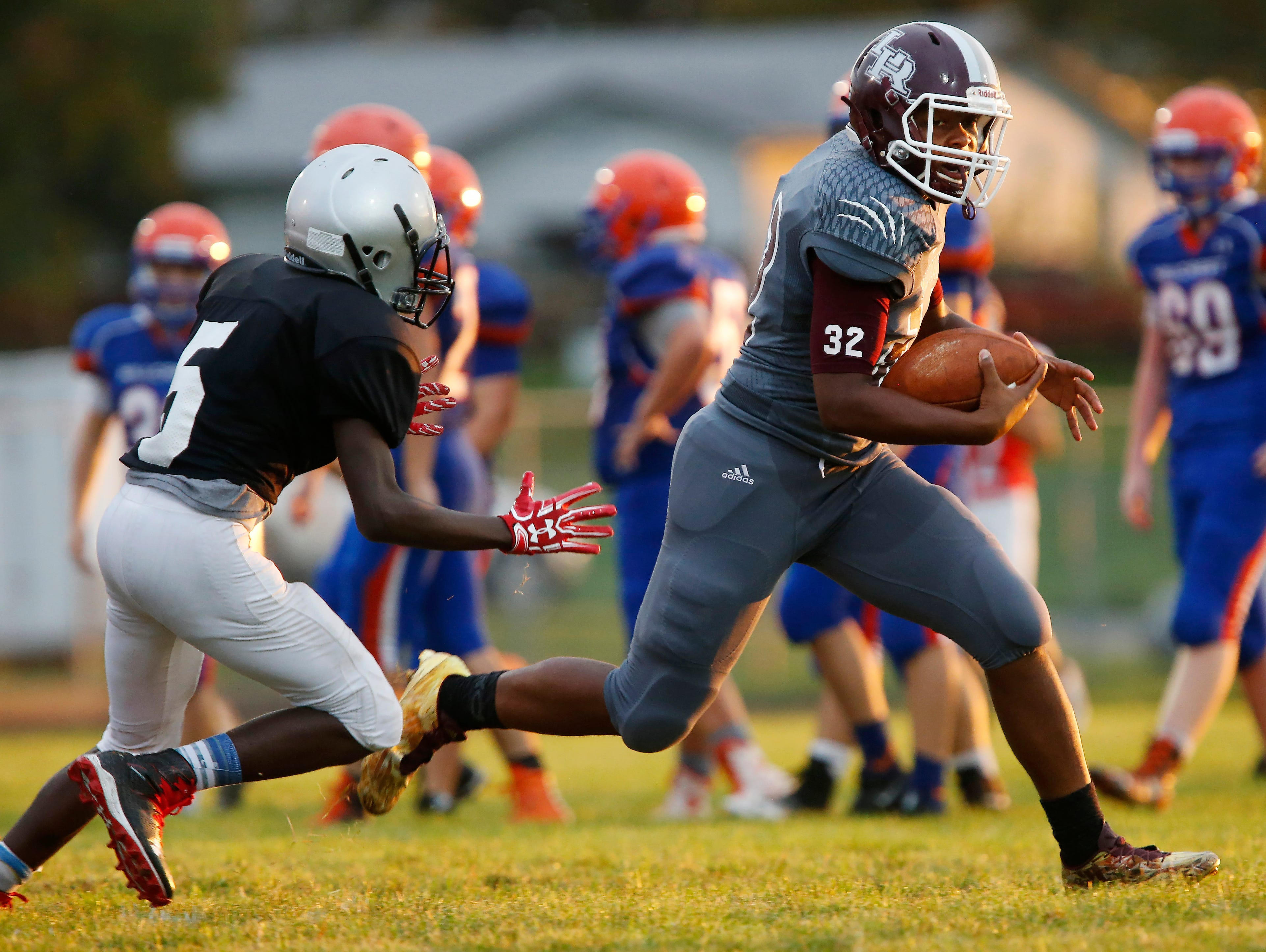 Dee Smith, of Logan-Rogersville (32), runs past a Central defender during the jamboree at Logan-Rogersville High School on Friday, August 12, 2016.
