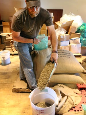 Jason Smith, a Roast Master at Just Love Coffee Roasters scoops out green coffee beans to roast on Tuesday, March 29, 2016.