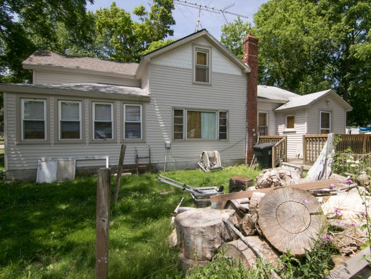 Yard waste and debris shown Tuesday, June 26, 2018 litter the yard of 816 McPherson St. in Howell, condemned for the past year.