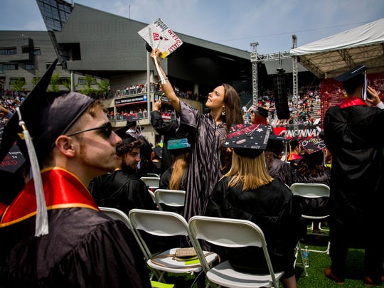 Renee Gooch holds her cap up to find her family at Nippert Stadium during the spring Commencement ceremony Saturday, April 29, 2017.