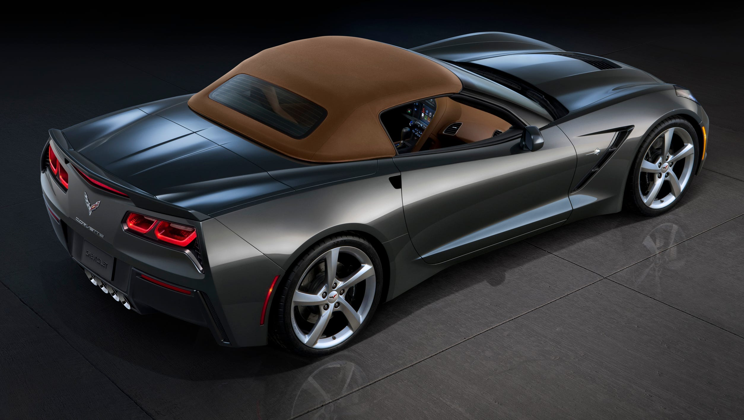 The 2014 Corvette Stingray convertible with the top up. It is a three-ply fabric top woth acoustic padding for noise control and a glass rear window.
