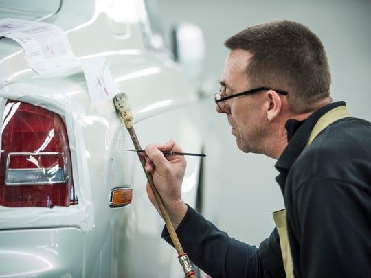 Mark Court paints a coachline on a Rolls-Royce Serenity