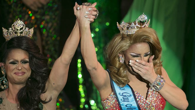 2015 Miss Gay Arizona Nevaeh McKenzie (L) lifts the hand of this year's winner, Savannah Stevens as she reacts to winning the crown during Miss Gay Arizona 2016 on June 26, 2016 in Phoenix.