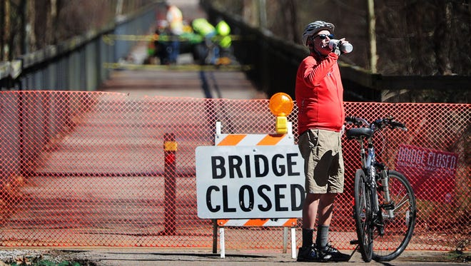Marc Stegman stops for a break on the east side of the Shelby Farm Greenline's bridge over the Wolf River Monday afternoon. Warmer weather notwithstanding, a section of the multi-use trail is closed this week to allow for maintenance work on the bridge.