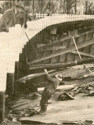 Jerry Farrar, superintendent for the highway department, examines the wreckage of the Mellow Moon Skating Rink.