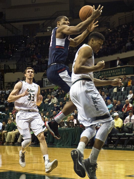 South Florida's Ruben Guerrero (33) looks on as teammate Angel Nunez, right, fouls Connecticut's Rodney Purvis, center, during the first half of an NCAA college basketball game Thursday, Feb. 25, 2016 in Tampa, Fla. (AP Photo/Steve Nesius)