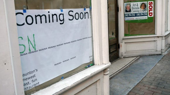 A coming soon sign with a hang man game gives passerby's