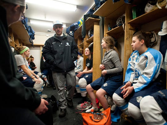 South Burlington girls hockey coach Jake Orr, center, addresses his team after the Rebels' 4-3 win over BFA-St. Albans on Saturday, Feb. 7, 2014.