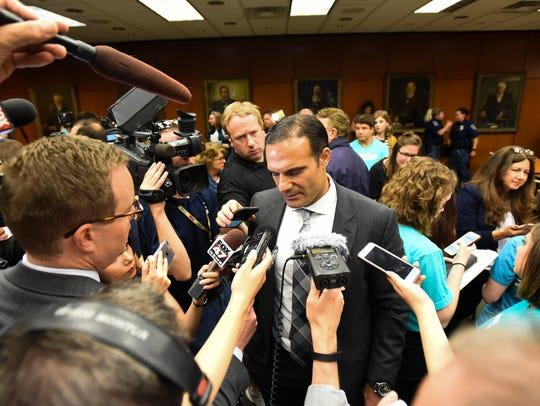 A bevy of reporters surround MSU Trustee Brian Mosallam,