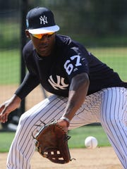 At third base, Miguel Andujar makes a play on a ground ball during defensive drills.