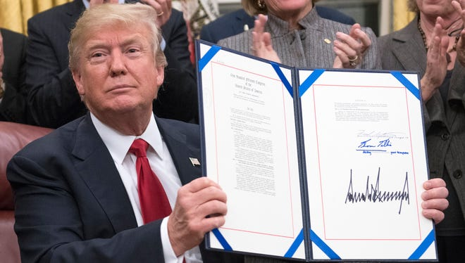 President Donald J. Trump signs a bipartisan bill to stop the flow of opioids into the United States in the Oval Office of the White House January 10.