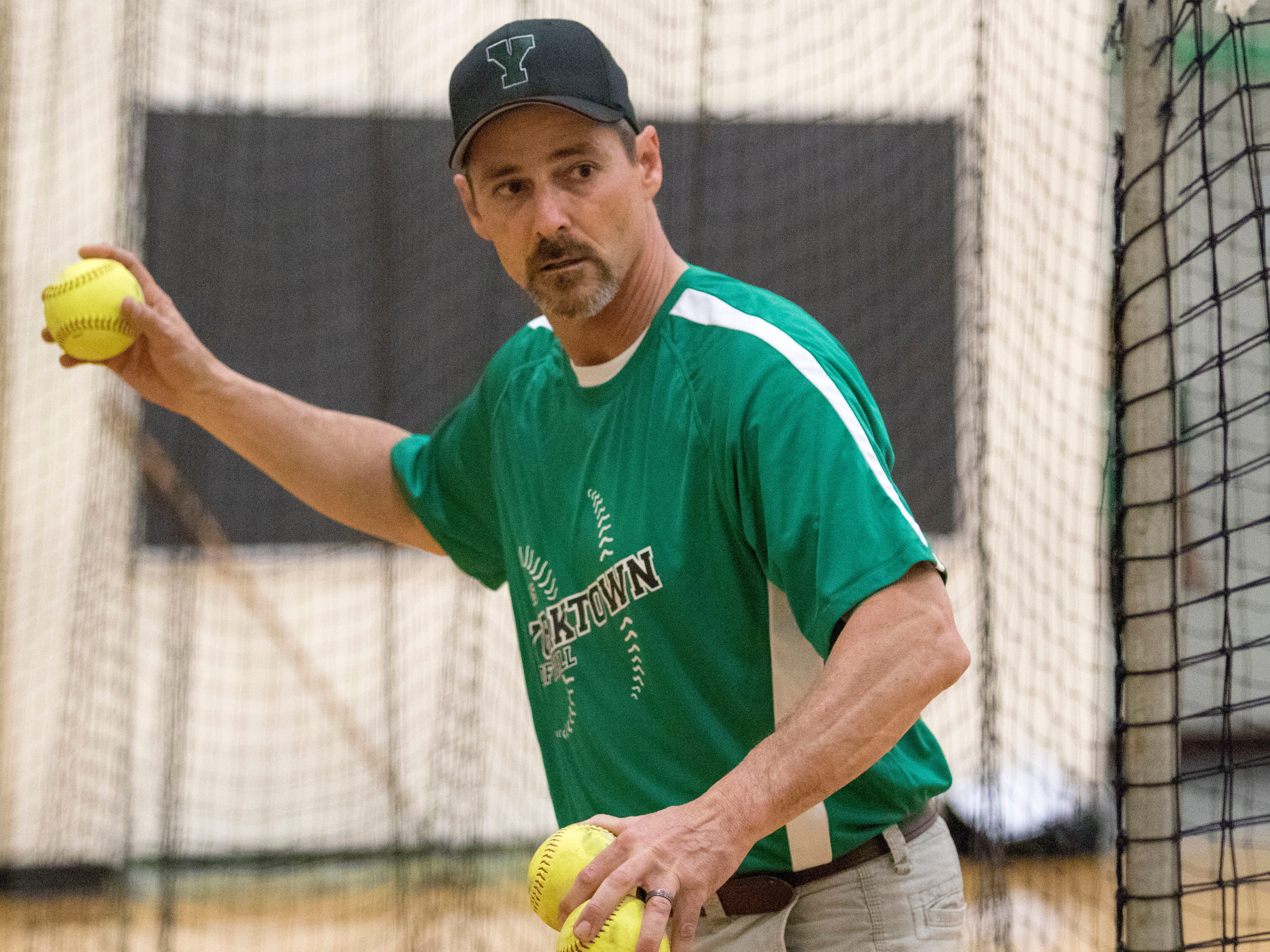 Coach Jeff Berger works with members of the Yorktown softball team at practice on Thursday. Berger is new to the team, but coached at Cowan in previous seasons.
