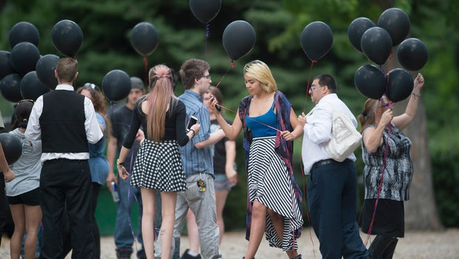 """Family and friends of Heather """"Helena"""" Hoffmann prepare for a balloon release during a memorial service for the 23-year-old woman at City Park on Thursday, June 29, 2017. Hoffmann was found dead on June 21 in Sheldon Lake."""