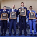 Newly-inducted National Baseball Hall of Famers Craig Biggio, John Smoltz, Randy Johnson and Pedro Martinez hold their plaques after an induction ceremony at the Clark Sports Center on Sunday, July 26, 2015, in Cooperstown, N.Y. (AP Photo/Mike Groll)