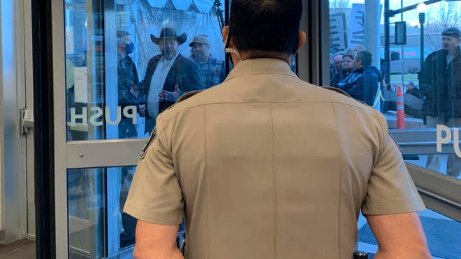 Anti-government activist Ammon Bundy, wearing a cowboy hat, yells through the closed Ada County Courthouse door at law enforcement officers inside Monday, when Bundy was scheduled to stand trial. People are required to wear face coverings while at the Boise, Idaho, courthouse because of the coronavirus pandemic, but Bundy and several others were protesting the mask requirement.