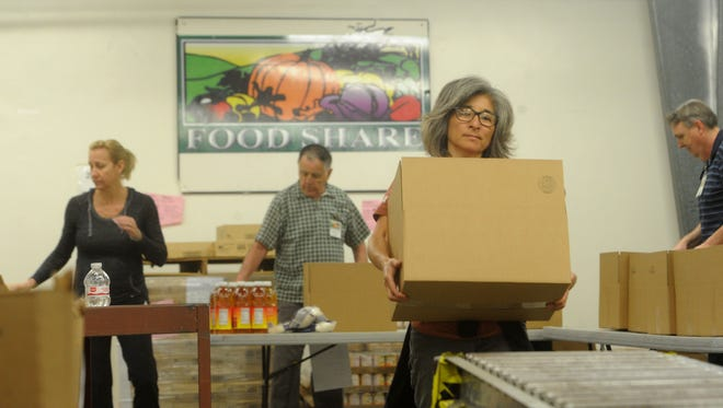 """Volunteer Janis McCann carries a box filled with food at FOOD Share of Ventura County. These """"Senior Kits"""" were to be distributed to income-qualifying participants 60 and older."""