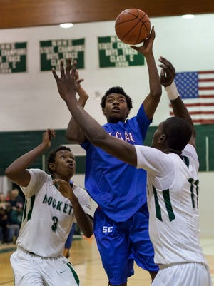 St. Clair sophomore Eric Williams takes a shot over New Haven senior Austin Sherrell and junior Innocent Nwoko during a basketball game Thursday at New Haven High School.