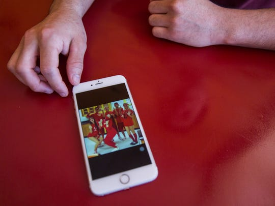 """Rodrigo Torres-Giusti shows a photo of him and his friends at Marjory Stoneman Douglas High School while at Gustitos Bakery on Thursday, Feb. 15, 2018. """"When I think of Douglas, I think of good memories,"""" said Torres. """"To think that so many kids won't be able to say the same hurts."""""""