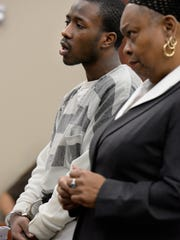 Timothy Minor III apologizes for his actions in court in Lansing on Wednesday before his  sentencing on two weapons charges in connection with a 2013 shooting incident near Sexton High School.  At right is his attorney Constance Ross.