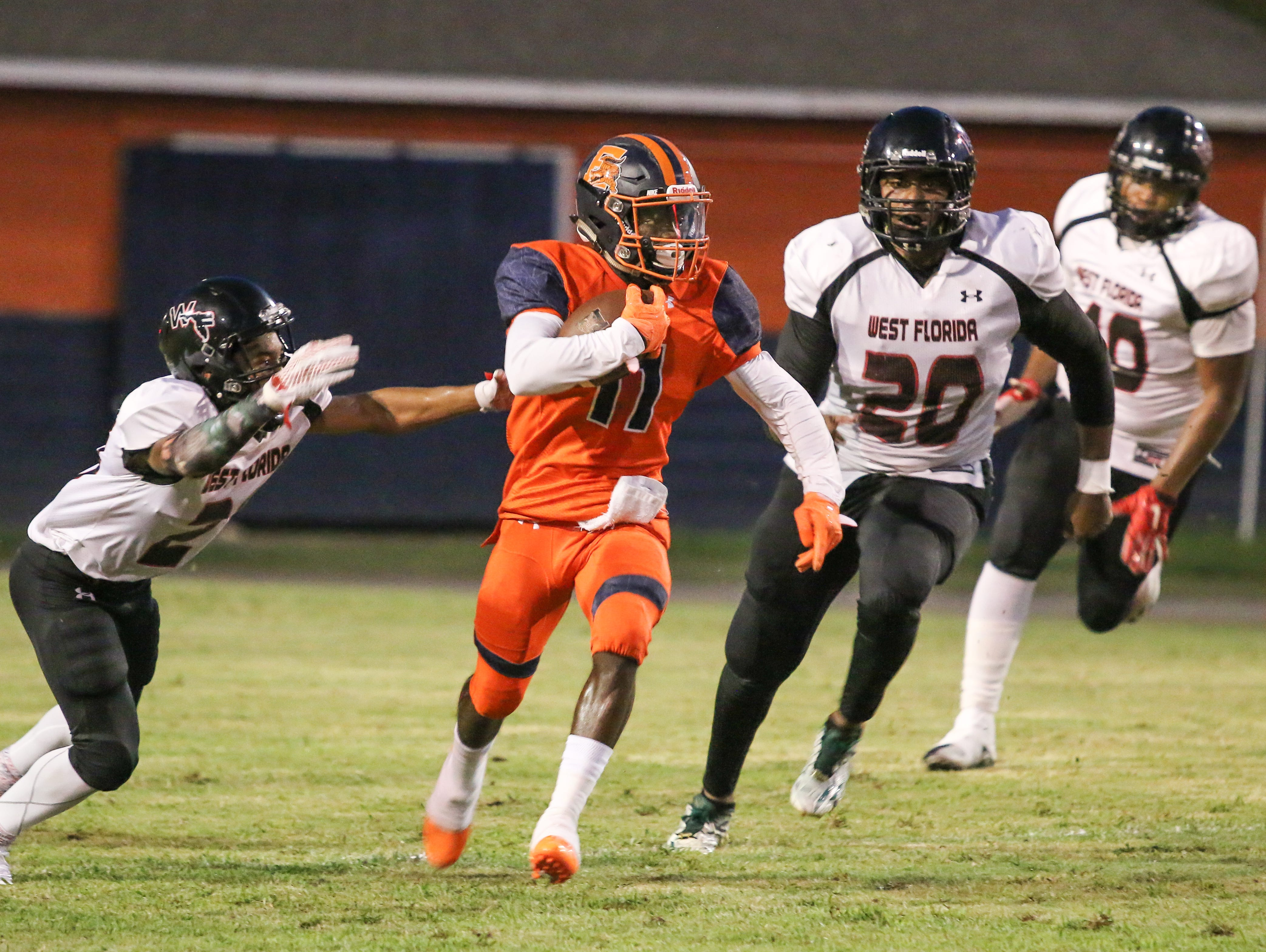 Escambia's Martin McGhee (11) races past the West Florida defenders Thursday night at Escambia High School's Emmitt Smith Field.