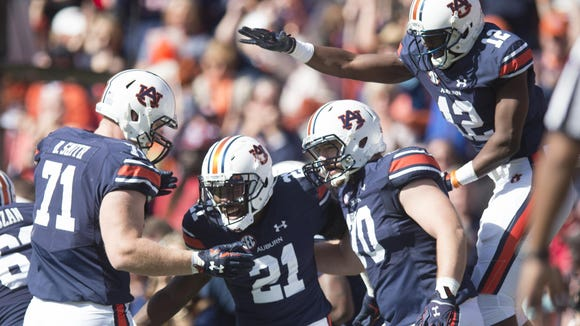 Auburn Tigers running back Kerryon Johnson (21) celebrates with Auburn Tigers offensive lineman Braden Smith (71), Auburn Tigers offensive lineman Robert Leff (70) and Auburn Tigers wide receiver Jonathan Wallace (12) after scoring a touchdown during the the NCAA football game between Auburn Tigers and Georgia on Saturday, Nov. 14, 2015, in Auburn, Ala.